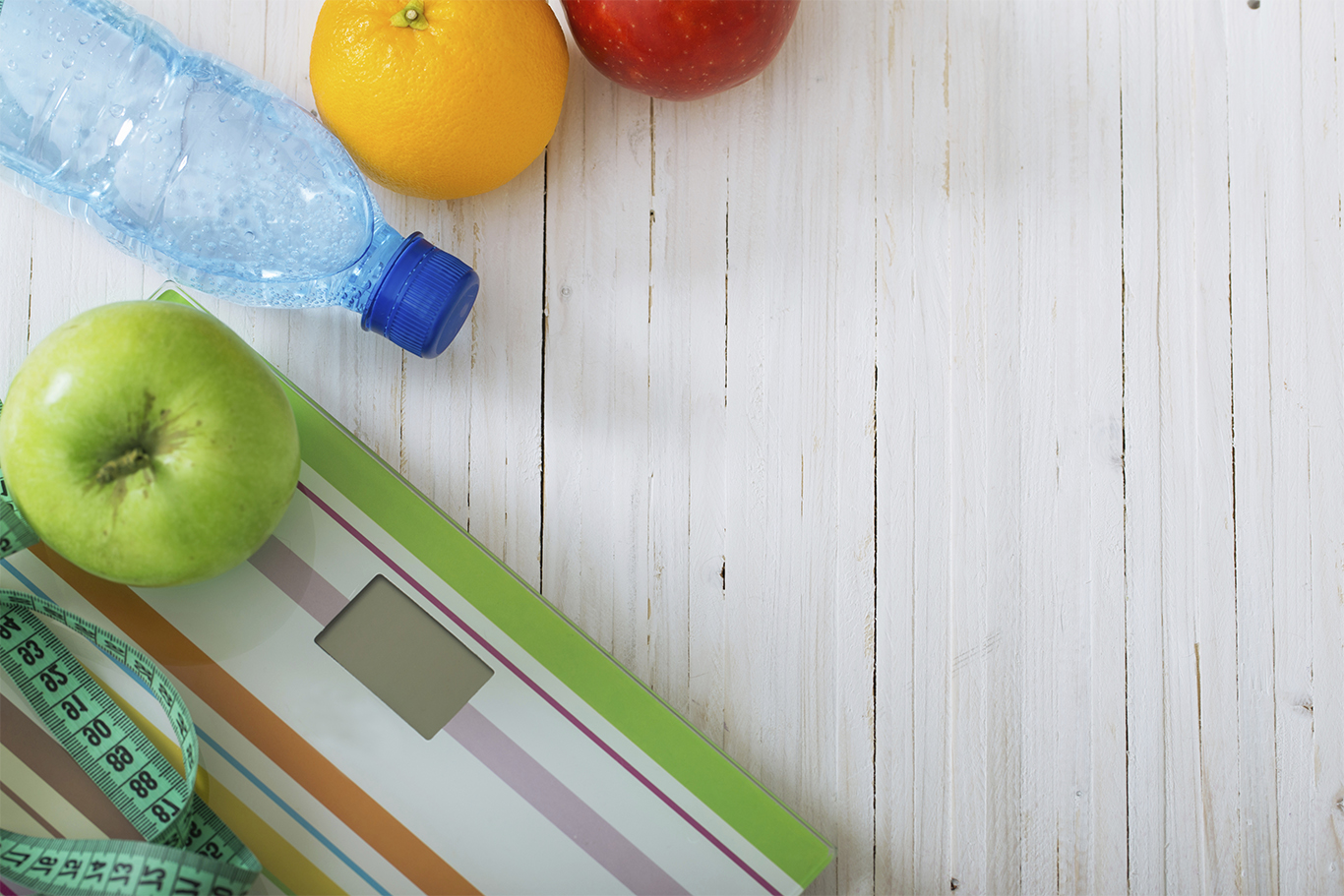 Scales, fruits, water on the white wooden background